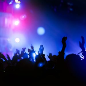 silhouettes of hand in concert.Light from the stage.confetti.the crowd of people silhouettes with their hands up.ribbon